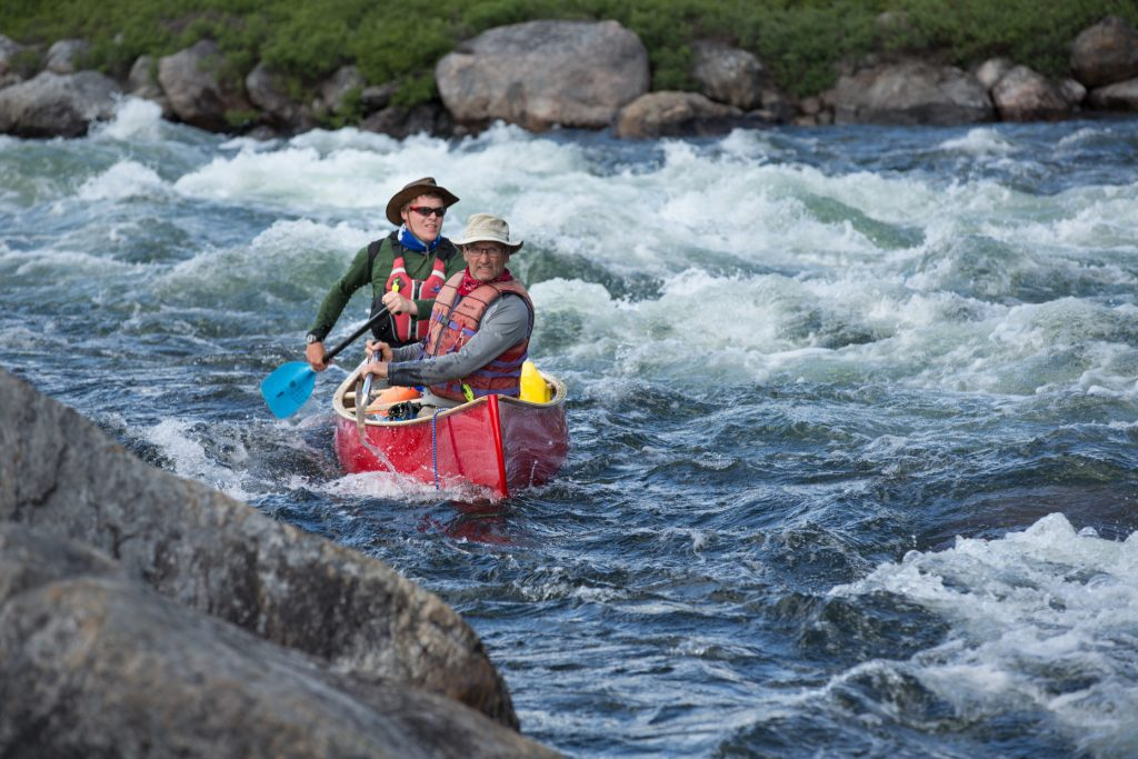 Yellowknife, NWT - Jack Stefanyk pulls a fast bow cross draw as Rylie Braun cooly tillers through a rough section on the Yellowknife River.